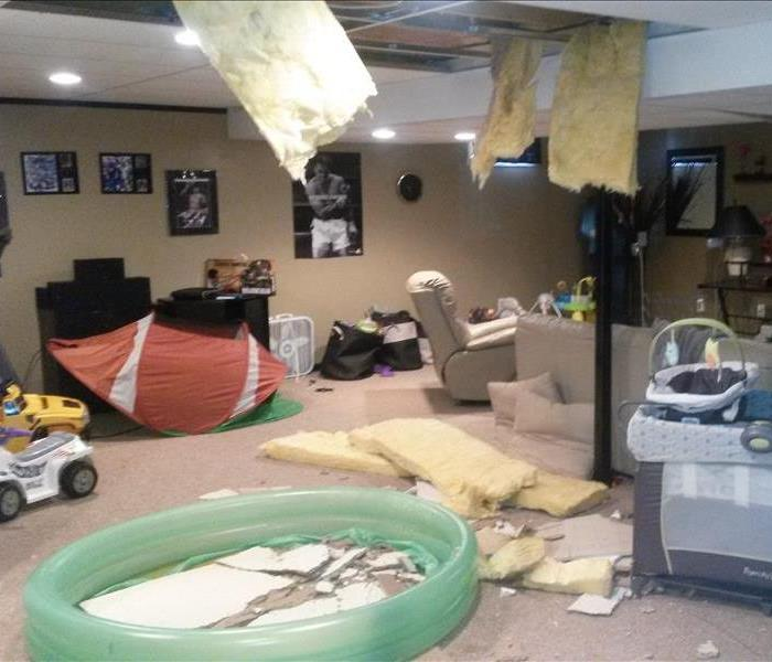 Ceiling collapsed in basement with water and furniture everywhere
