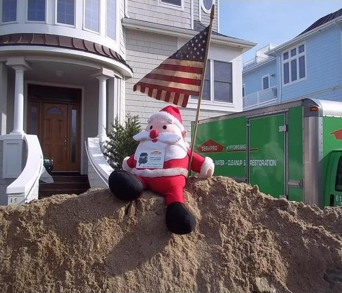 Stuffed Santa Claus holding American Flag in front of SERVPRO box truck