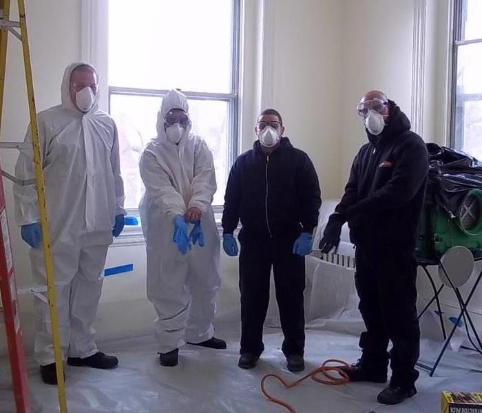 Four People dressed in SERVPRO attire and masks at a job site