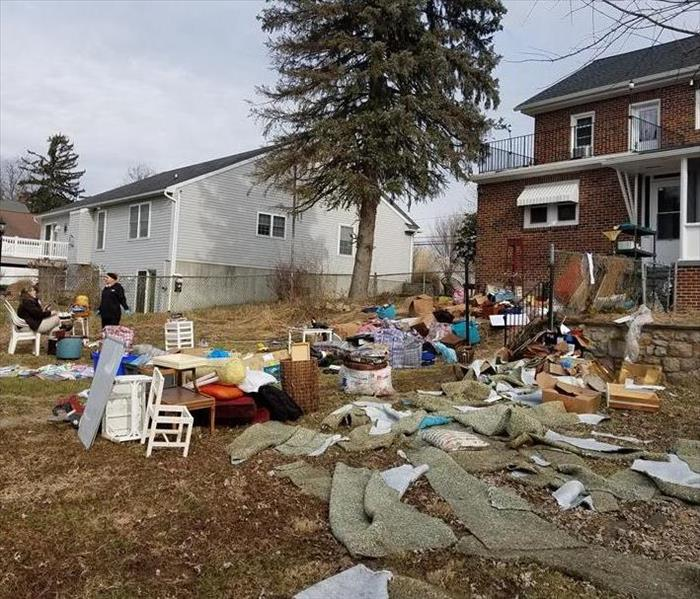 A yard cluttered with a home's damaged belongings