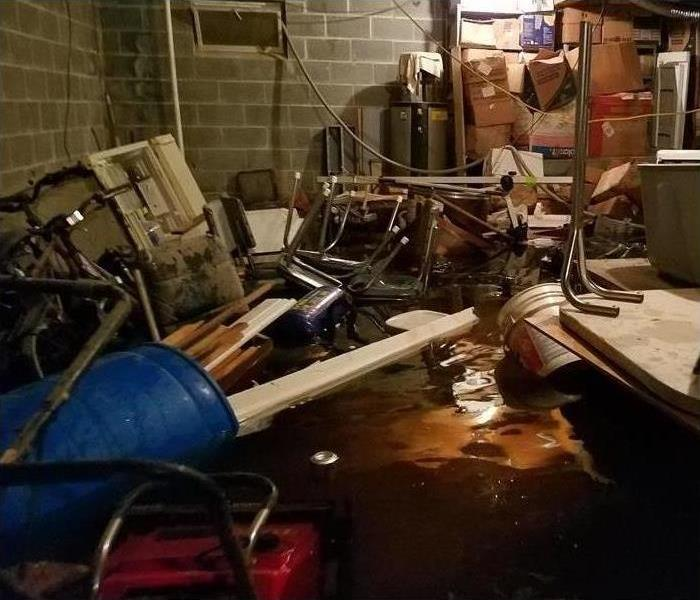 Flooded basement with floating debris everywhere